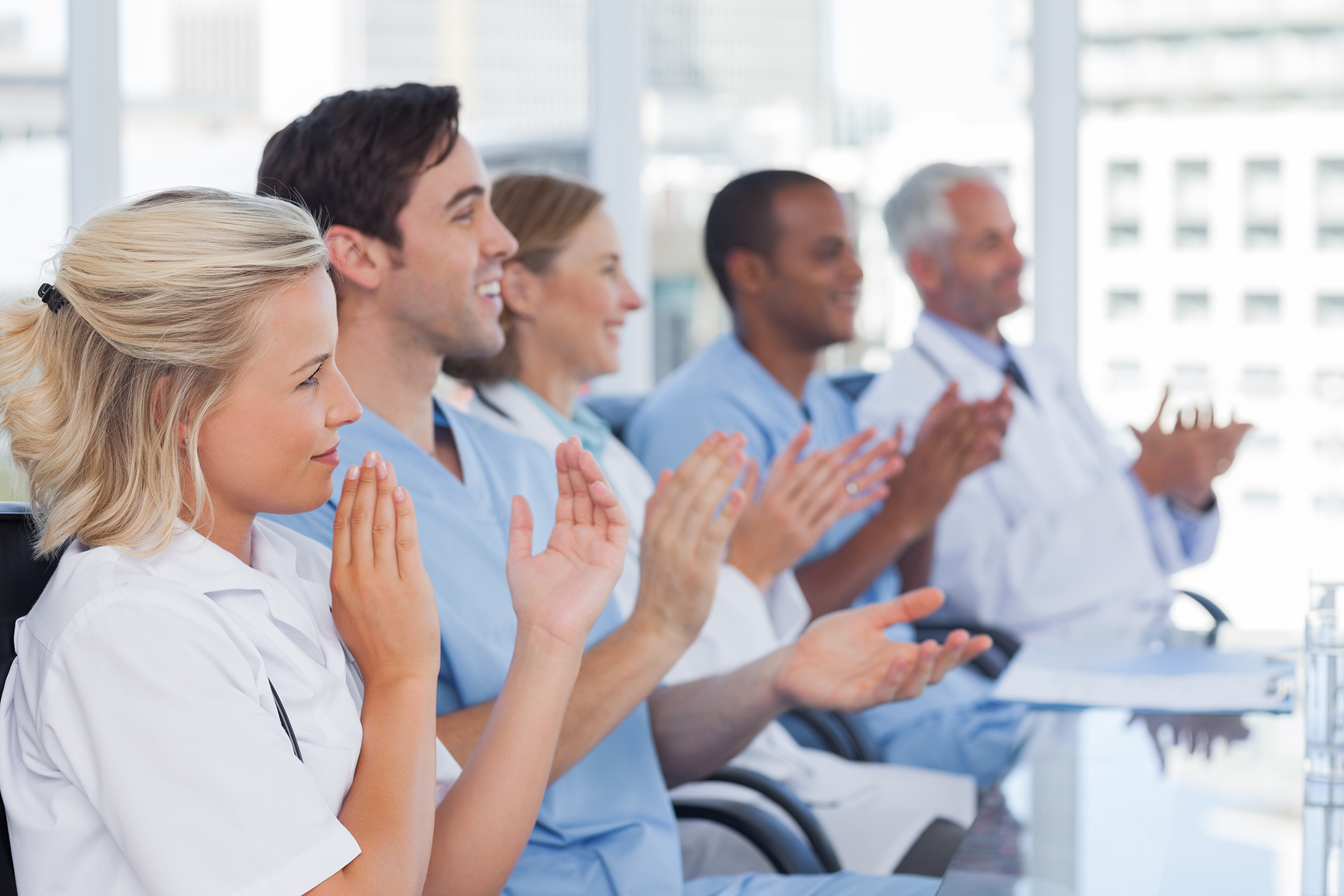 Medical team clapping hands during a conference
